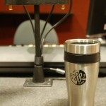 WJCU travel tumbler mug on a desk