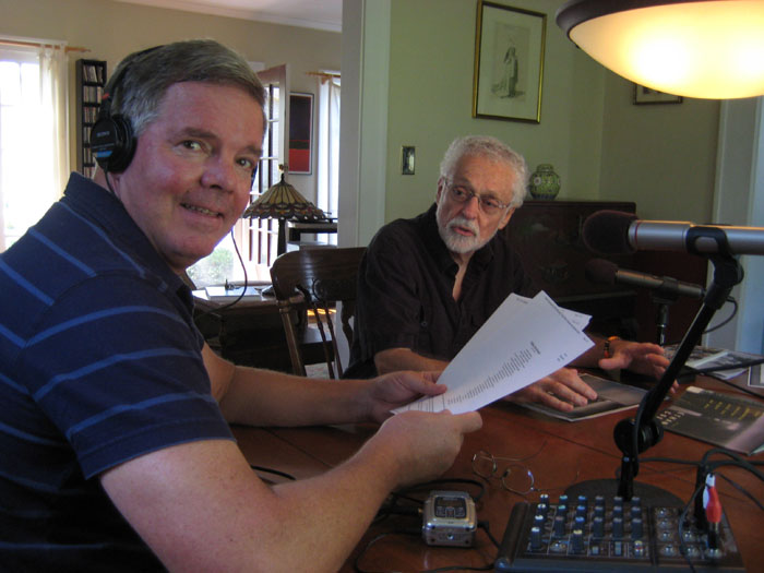 George Bilgere at a table with a microphone with John Donaghue sitting nearby